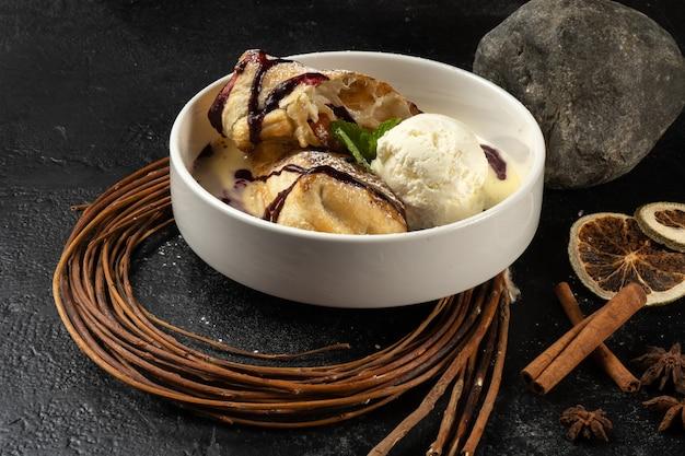 아이스크림과 슈트 루델. 베리 소스와 바닐라 아이스크림 스쿱을 곁들인 클래식 스위트 디저트