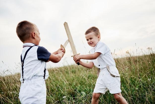勝つために苦労します。フィールドで木製の剣で遊んで楽しんでいる2人の子供。