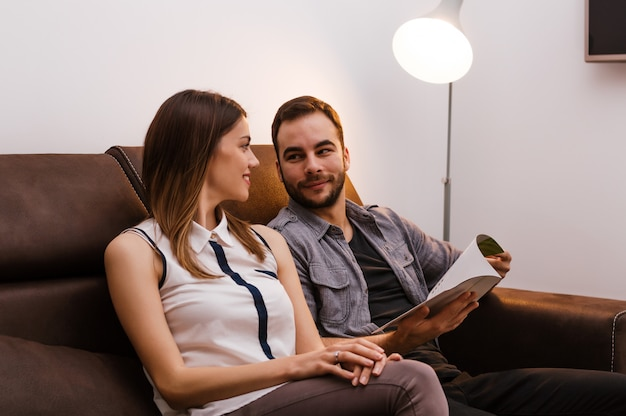 Stubble boy showing documents to his girlfriend