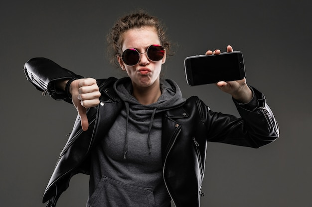 Stubborn caucasian girl with rough facial features in a black jacket shows her phone and doesn't like it isolated on black wall