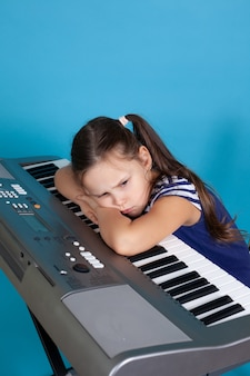 Stubborn girl with her head on synthesizer keys, doesn't want to learn playing a musical instrument