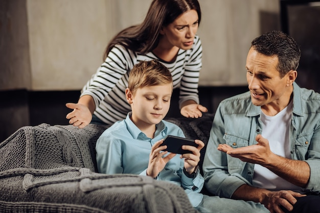 Упрямый ребенок. светловолосый мальчик предподросткового возраста безмятежно играет по телефону, не обращая внимания на то, что родители ругают его и просят положить трубку