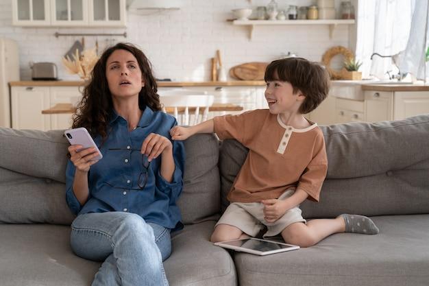 Упрямый сын раздражает мать дома, усталая мама пытается прочитать сообщение, сидя на диване с непослушным ребенком