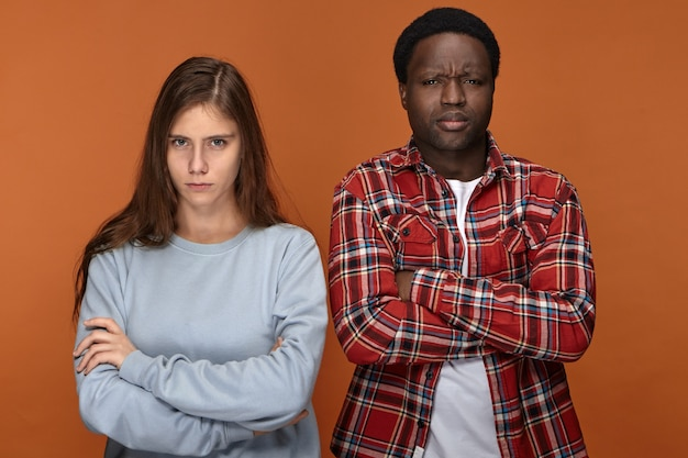 Stubborn young interracial couple having disagreement about plans on weekend with grumpy facial expressions, keeping their arms crossed, frowning, not talking to each other