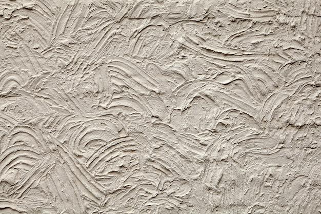 粗い漆喰と半円形の溝のある漆喰の壁。