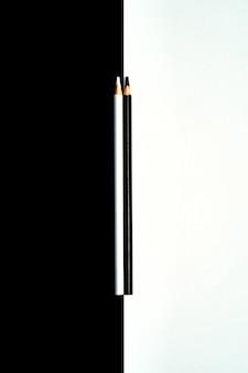 黒と白の背景に分離された黒と白の色鉛筆を立ち往生