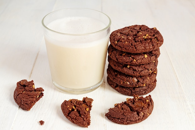 Stuck of chocolate brownie cookies and glass of coconut milk on wooden table. homemade pastry