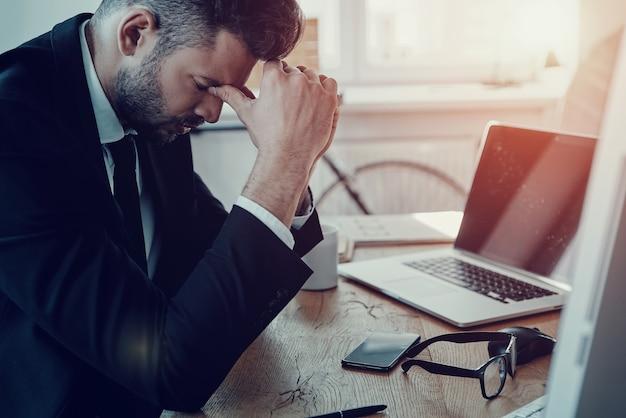 オフィスで立ち往生。オフィスに座って鼻をマッサージする正装で疲れた若い男