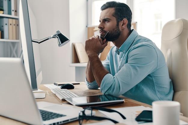オフィスで立ち往生。オフィスに座って目をそらしている若い現代実業家