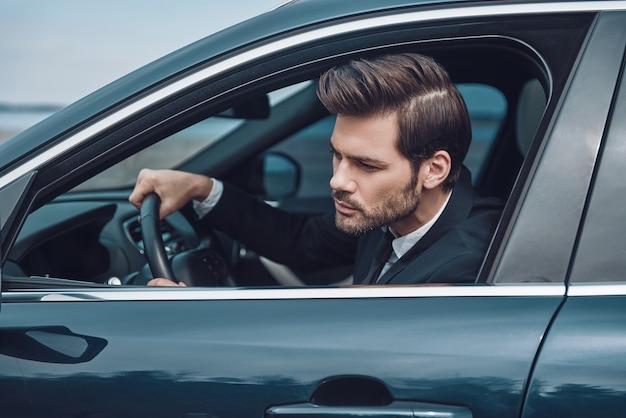 渋滞に巻き込まれました。車を運転しながらまっすぐに見えるフルスーツのハンサムな若い男