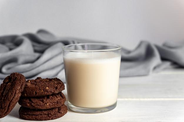 木製の背景にチョコレートブラウニークッキーとココナッツミルクのガラスの立ち往生。自家製ペストリー