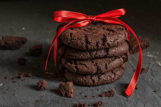 黒いコンクリートの表面に赤いリボンとチョコレートブラウニークッキーのスタック