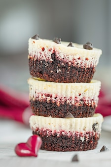 Stuck of three irresistible red velvet mini cheesecakes with chocolate drops