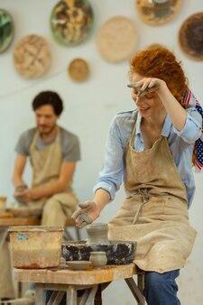 スタッディングの側面。鍋を作っている間、汚れた手で額から汗を拭く疲れた女の子を笑う