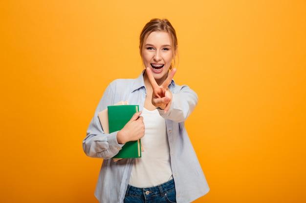 本を持って平和のジェスチャーで幸せな若い女性studen。