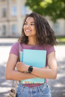 Студент. фотография девушки в розовой футболке с учебниками в руках