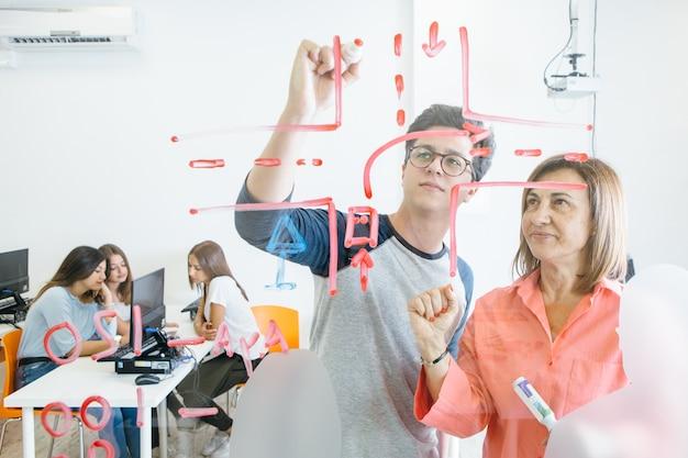 Студент и учитель рисуют на доске