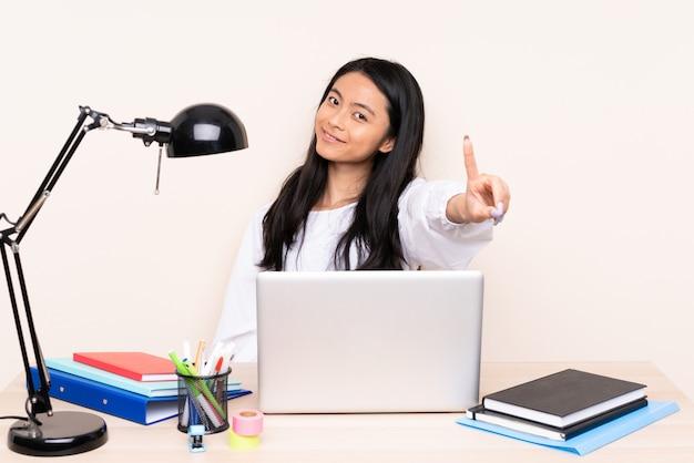 ベージュ色の背景を表示して指を離して分離されたラップトップで職場で学生アジアの女の子