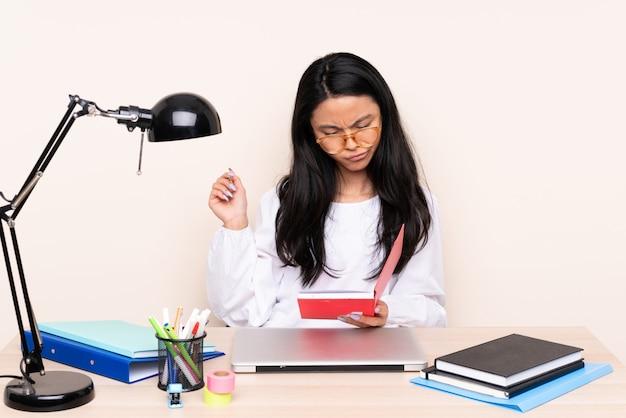 Студент азиатская девушка на рабочем месте с ноутбуком, изолированных на бежевом фоне