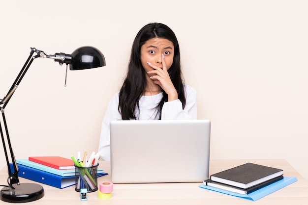 ベージュで隔離されたラップトップを持っている職場の学生アジアの女の子は、右を見ながら驚いてショックを受けました
