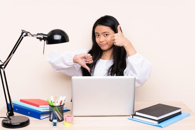 Девушка студента азиатская в рабочем месте с компьтер-книжкой на бежевой стене делая хороший плохой знак. не определились между да или нет