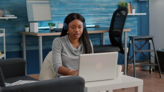 Студент-блогер с темной кожей надевает наушники, работая дома, в статье социальных сетей