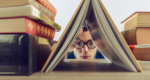 Student boy reprimanded at the school hidden between books