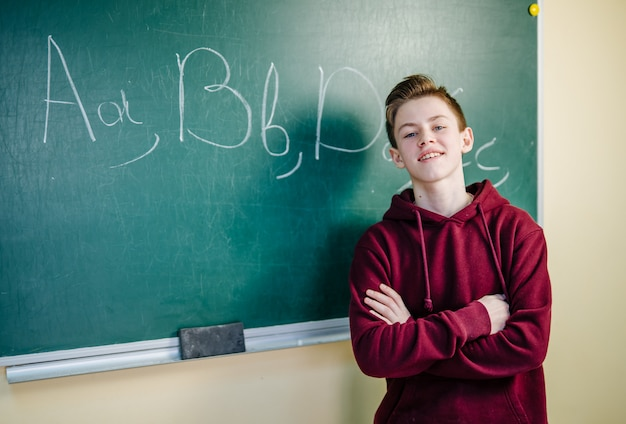 Student boy standing in front of chalkboard in the classroom at school