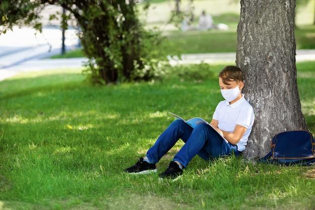 マスクを身に着けている学生の少年が公園に座って、covid19パンデミックの間に本を読んでいます