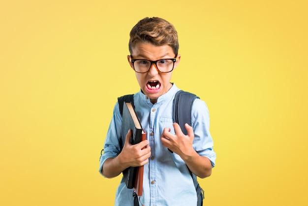 Студенческий мальчик с рюкзаком и очками раздраженно сердился в ярости. обратно в школу