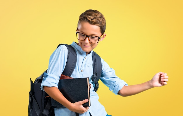 Student boy with backpack and glasses listening to the music and dancing. back to school