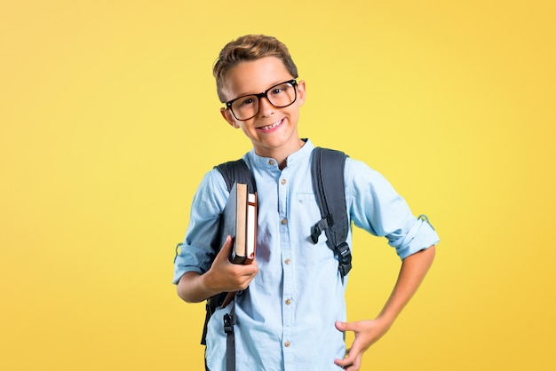 Student boy with backpack and glasses posing with arms at hip on yellow background.