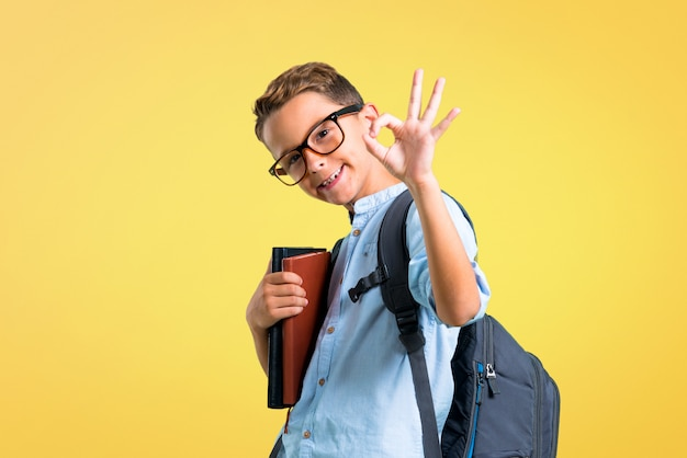 Student boy with backpack and glasses showing an ok sign with fingers. back to school