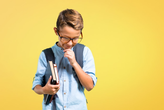 Student boy with backpack and glasses standing and looking down on yellow background.