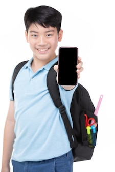 Student boy with backpack and stationery holding cell phone .