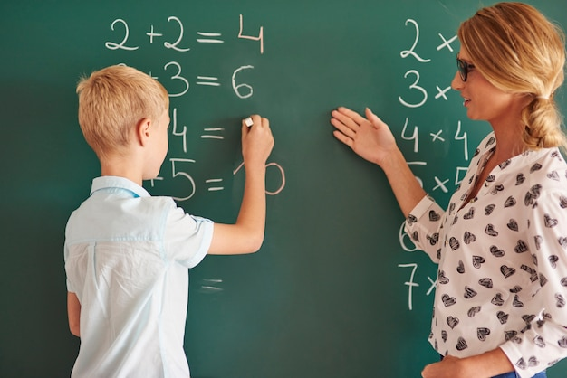 Student boy with chalk next to the chalkboard