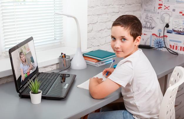 自宅の先生とビデオ通話を持つラップトップを持つ学生少年。