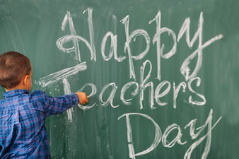 Student boy writing happy teachers day on blackboard
