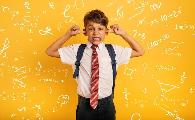 学生の子供は、騒音を聞きたくないので耳をふさいでいます。