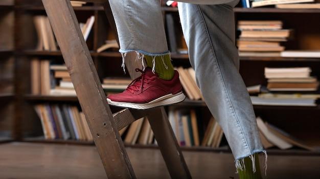 학생은 도서관 책장에 있는 계단을 올라갑니다.