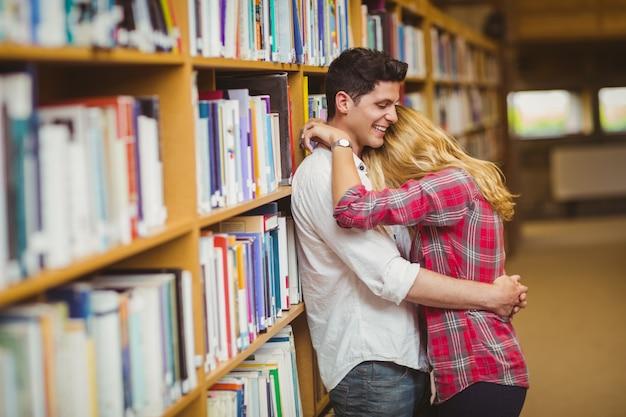 図書館でお互いを受け入れている学生カップル