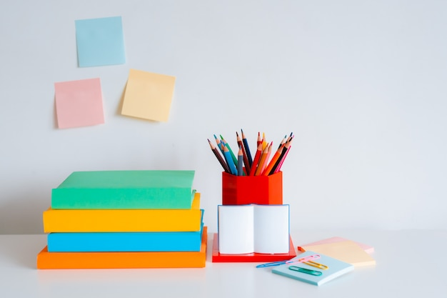 Student creative desktop layout with colorful stationery, colored pencils and bright books on a white wall background.