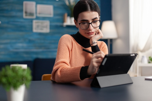 学生デザイナーが居間の机に座ってデジタルタブレットでスケッチを描く。、プロのデザインのペンレタッチドローを使用してグラフィックイラストで作業する引き出し