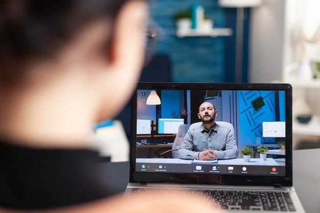 랩톱 컴퓨터를 사용하는 전자 학습 플랫폼에 대한 온라인 화상 통화에서 교사와 토론하는 학생. 거실에 앉아 코로나바이러스 격리 기간 동안 원격 교육을 받는 젊은 여성