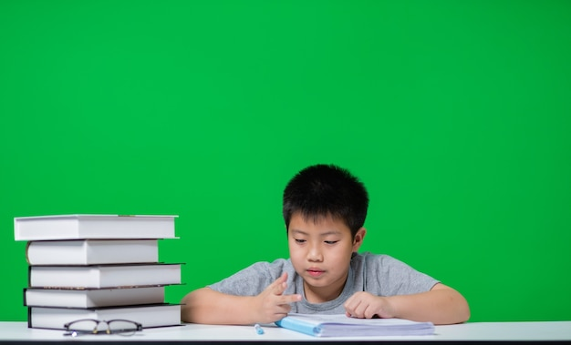 Student doing homework on green screen, child writing paper, education concept, back to school