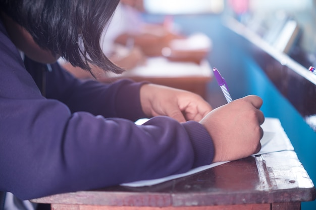 Student doing test or exam  in classroom of school with stress
