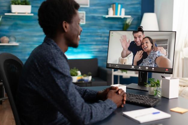 Студент с удовольствием проводит время с удаленными друзьями, обсуждая идеи управленческих проектов во время онлайн-конференции по видеосвязи. человек, имеющий виртуальную видеоконференцию во время изоляции от коронавируса