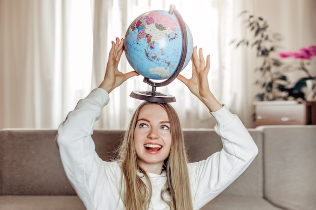 Student exchange. study abroad concept. young joyful student girl dreaming of a travel and holding globe above her head