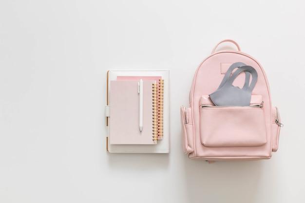 Студенческий женский рюкзак, полный школьных принадлежностей, изолированных с копией пространства. вернуться к школьной концепции