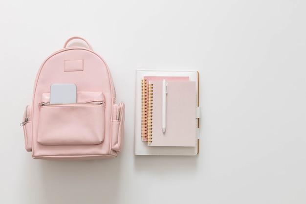 Студенческий женский рюкзак, полный школьных принадлежностей, изолированных с копией пространства. концепция снова в школу